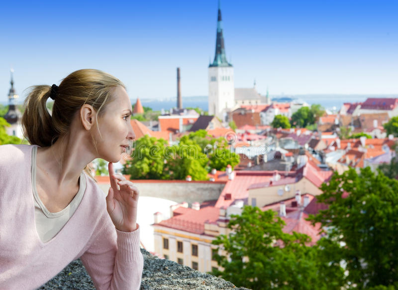 Young attractive woman admires roofs of houses of the Old city from an observation deck. Tallinn. Estonia. royalty free stock photo