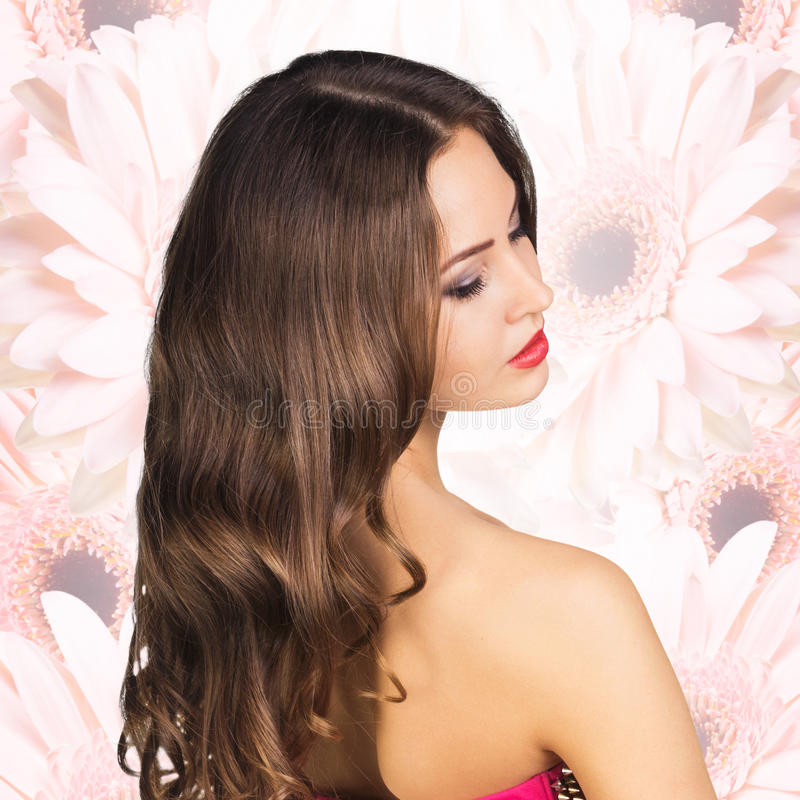 Young attractive woman appears from bouquet. royalty free stock image