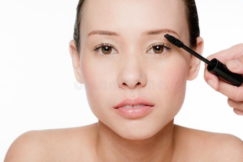 Young And Attractive Woman Applying Mascara Royalty Free Stock Images
