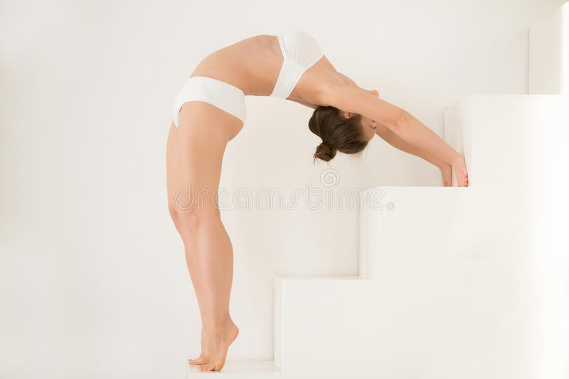 Young attractive woman in Ardha Chakrasana pose, white color bac stock photography