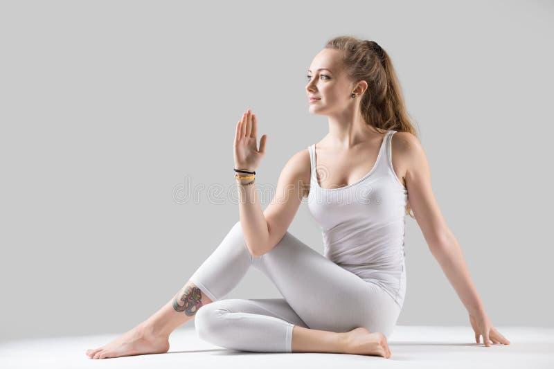 Young attractive woman in Ardha Matsyendrasana pose, grey studio royalty free stock image