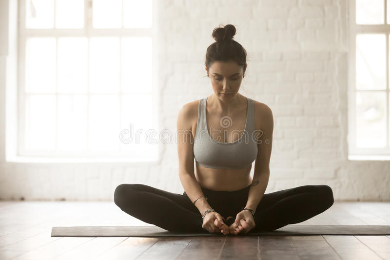 Young attractive woman in baddha konasana pose, white loft studi. Young attractive yogi woman practicing yoga concept, sitting in baddha konasana exercise royalty free stock images