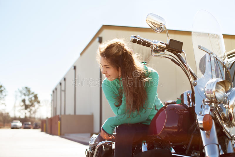 Young attractive woman with beautiful smile is sitting on red motorcycle royalty free stock image