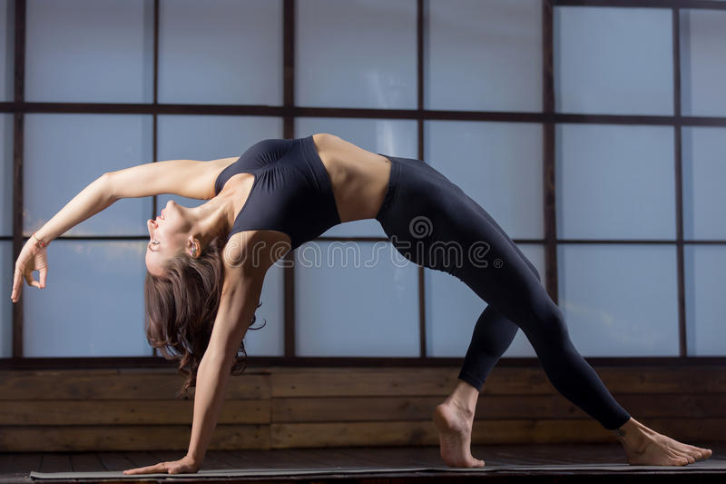 Young attractive woman in Bending Side Plank pose, evening pract stock image
