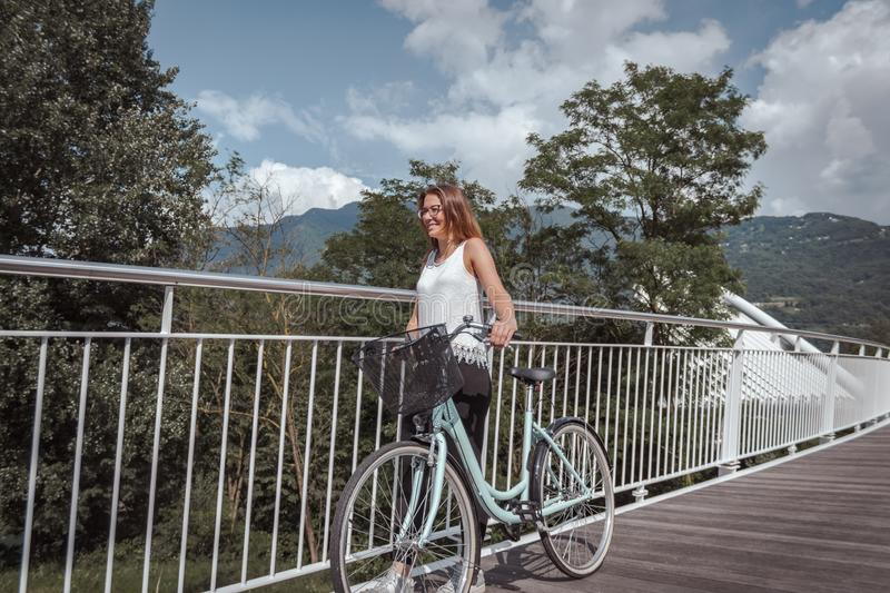 Young attractive woman with bicycle on a bridge royalty free stock photo