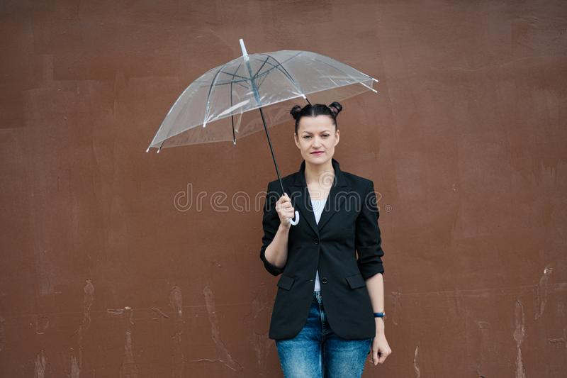 Young attractive woman in black jacket and blue jeans posing outdoor against background of building. royalty free stock images