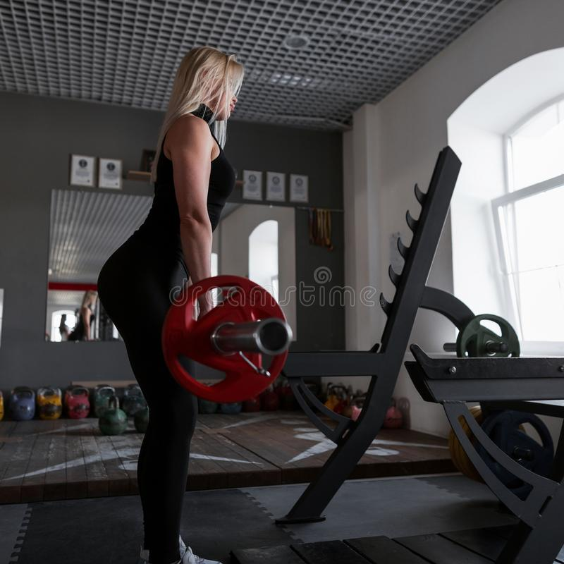 Young attractive woman in black sportswear in sneakers raises the barbell in training in the gym. Girl doing strength exercises. stock image