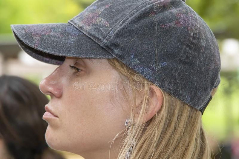 Young attractive woman with blond hair and a worn cap on her head - side view with a slight pout and a little sheen of sweat stock photography