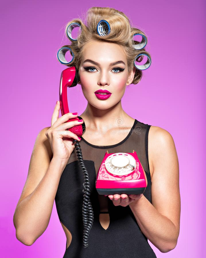Young attractive woman with blue culers using an old phone. Girl calmly calling by a vintage telephone royalty free stock image