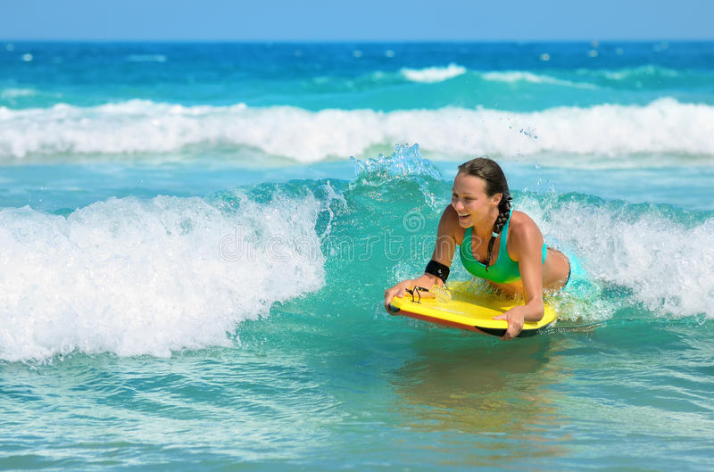 Young attractive woman bodyboards on surfboard with nice smile.  royalty free stock images