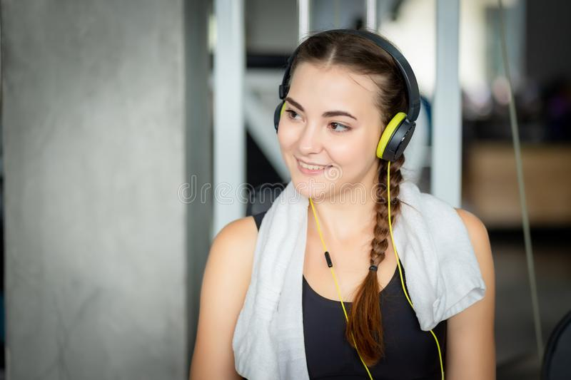 Young attractive woman caucasian sitting and listening to music by earphones connect to smart phone. stock photos