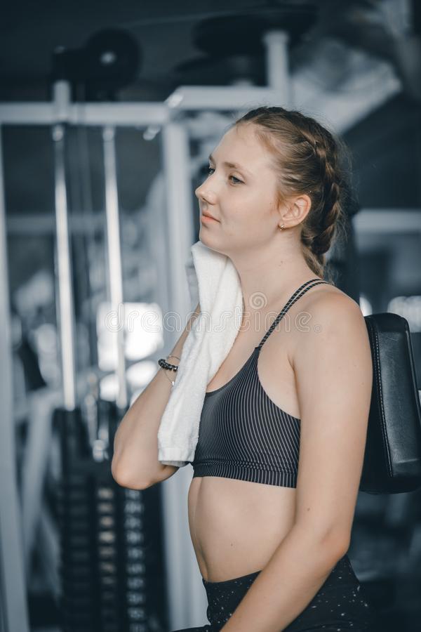 Young attractive woman caucasian sitting and using towel to wipe the sweat. Relaxation after hard workout in gym. Fitness concept stock image