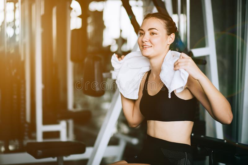 Young attractive woman caucasian sitting and using towel to wipe the sweat. Relaxation after hard workout in gym stock images