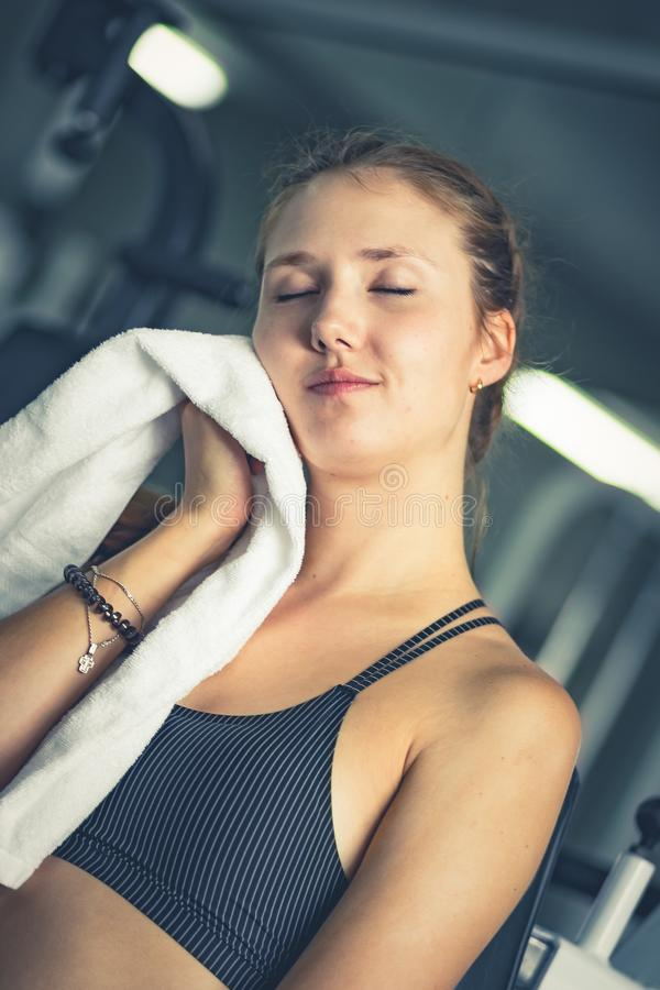 Young attractive woman caucasian sitting and using towel to wipe the sweat. Relaxation after hard workout in gym. stock image