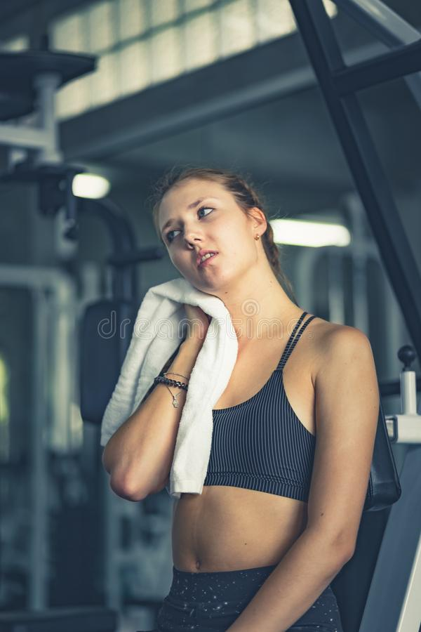 Young attractive woman caucasian sitting and using towel to wipe the sweat. Relaxation after hard workout in gym. stock photos