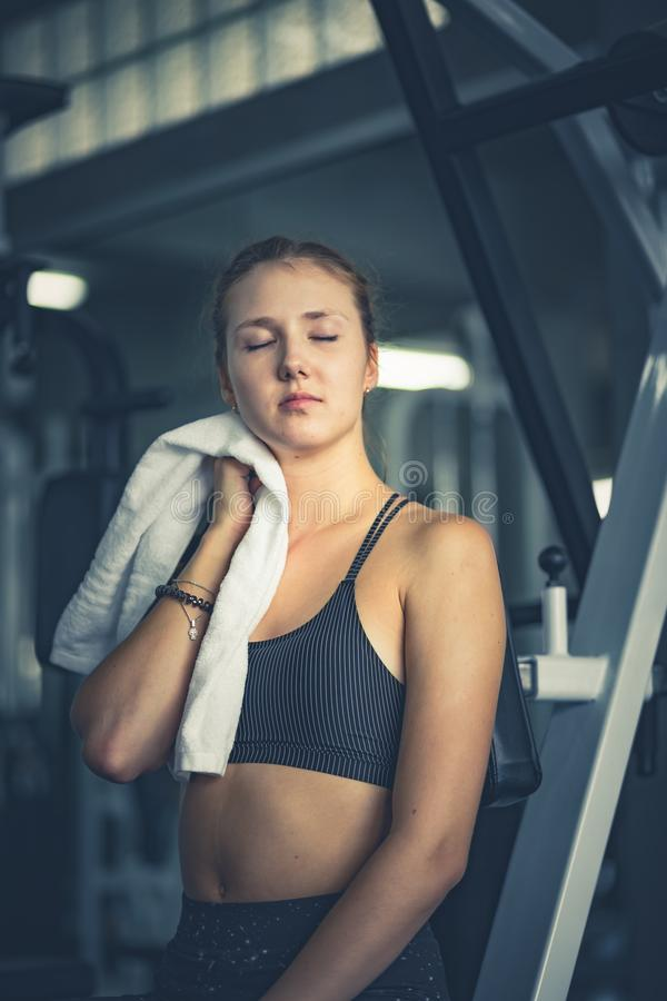 Young attractive woman caucasian sitting and using towel to wipe the sweat. Relaxation after hard workout in gym. royalty free stock image