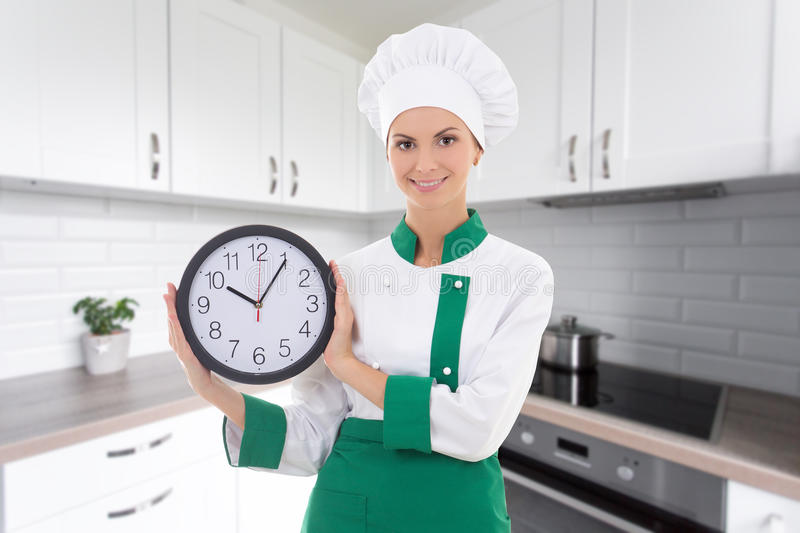 Young attractive woman in chef uniform with office clock in mode royalty free stock photography