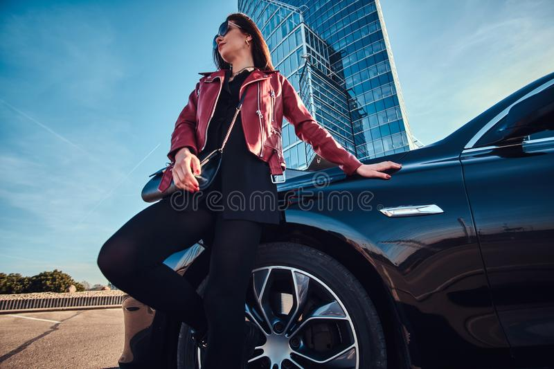 Young attractive woman is chilling in bright sunny day next to her car stock image