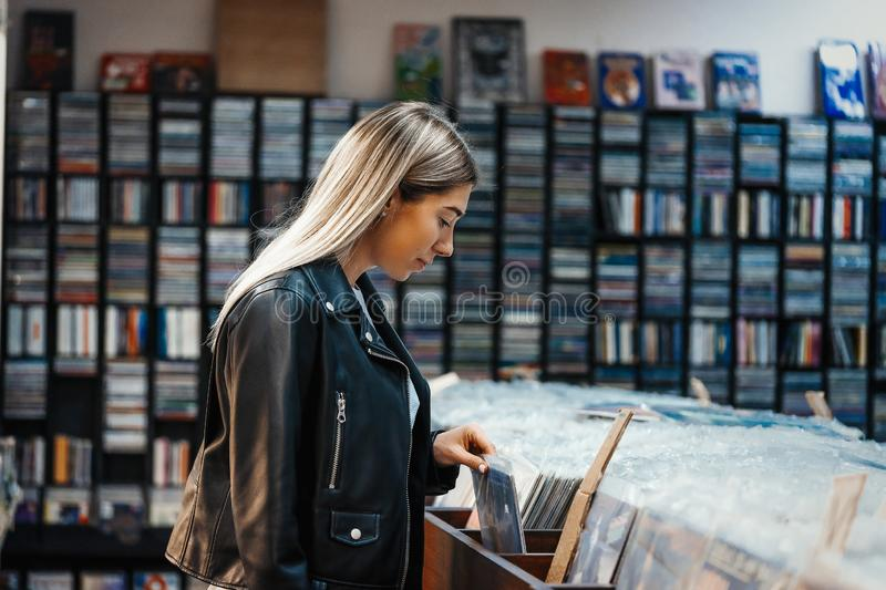 Young attractive woman choosing vinyl record in music record shop royalty free stock images