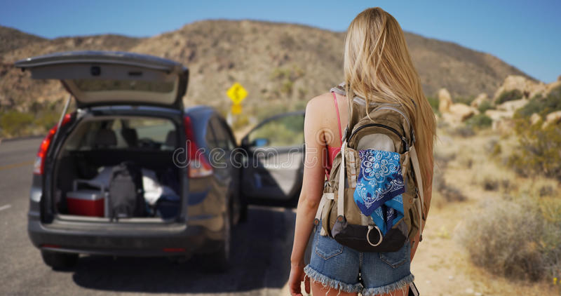 Young attractive woman comes across abandoned vehicle in the desert royalty free stock photo