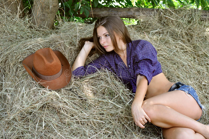 Young attractive woman in cowgirl style lying on haystack. In summer day stock photos