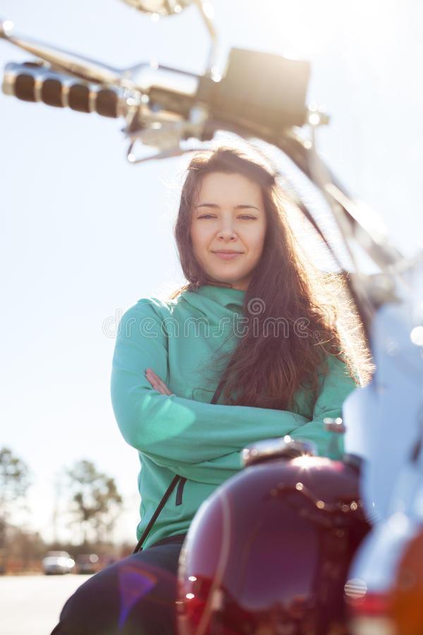 Young attractive woman with crossed hands is sitting on red motorcycle royalty free stock photo