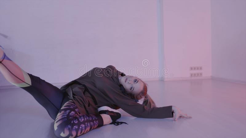 Young attractive woman dancing modern dance in dance hall. Action. Young woman full of energy and sexuality performs royalty free stock photos