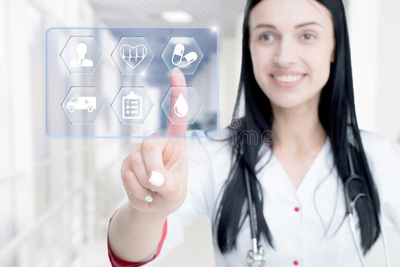 Young attractive woman doctor touching icon of media screen. stock photography