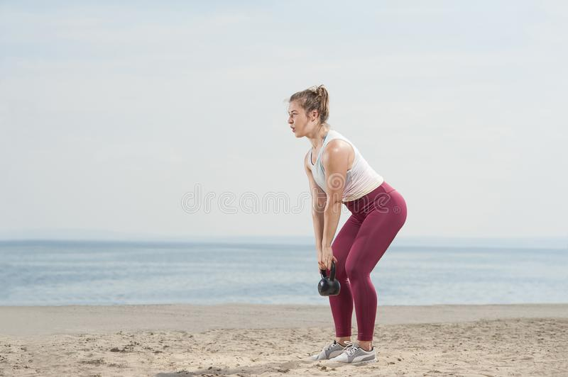 Young attractive woman doing kettle bell exercises outside stock photo