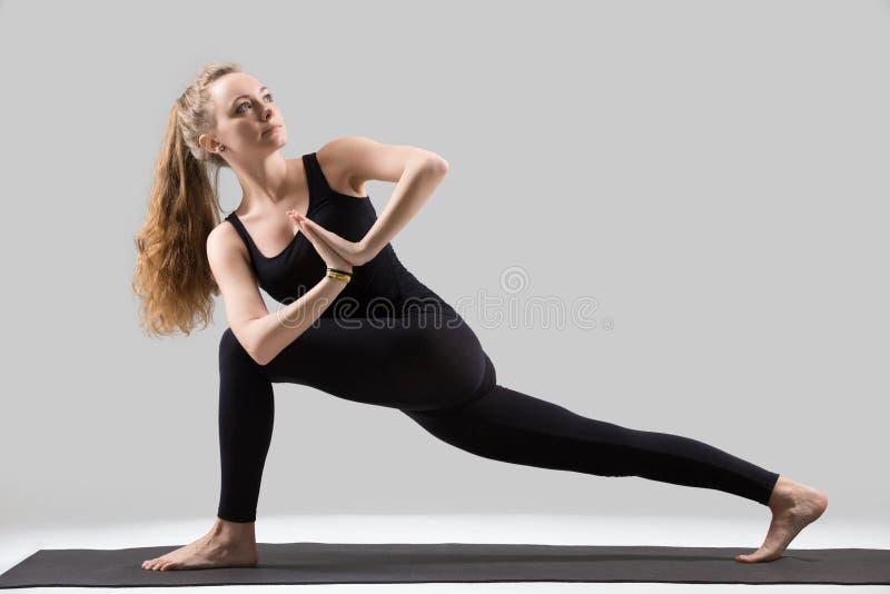 Young attractive woman doing Parivrtta Parsvakonasana pose, grey stock photo