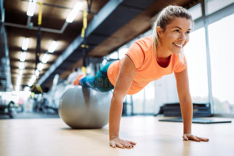 Young attractive woman doing push ups using ball royalty free stock images