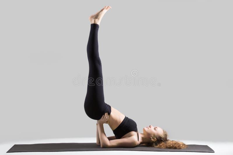 Young attractive woman doing Viparita Karani pose, grey studio b stock image