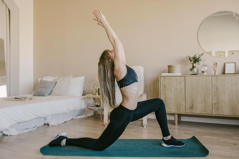 Young attractive woman doing yoga in her living room.Natural light ambient. stock photos