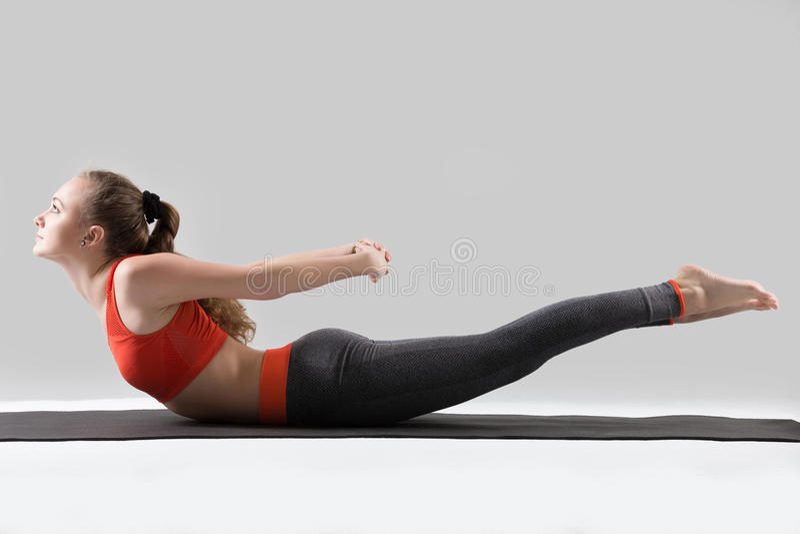 Young attractive woman in Double Leg Kicks exercise, grey studio. Young attractive woman practicing yoga, stretching in Double Leg Kicks exercise, Salabhasana stock photos