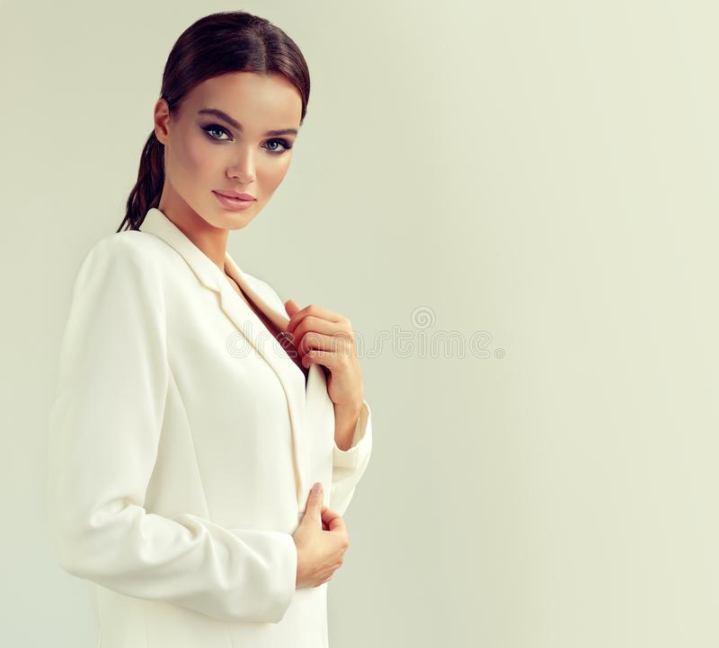 Young attractive woman dressed in a white suit jacket. Makeup and cosmetology. stock photos
