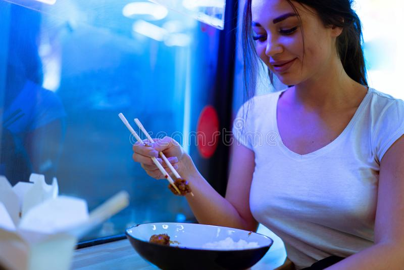 Young attractive woman eating asian food with chopsticks at cafe or restaurant. royalty free stock photos