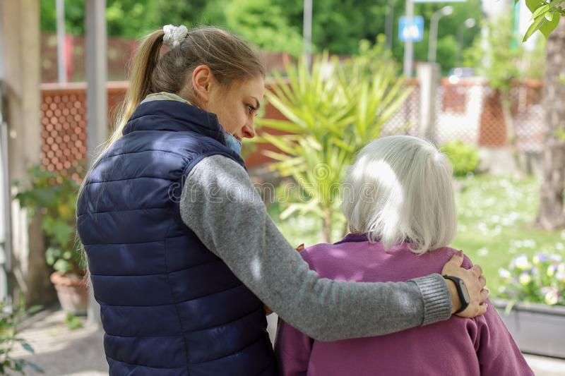 Young attractive woman embracing old grandmother outdoor. Female - generations - love royalty free stock photos