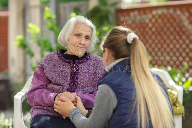 Young attractive woman embracing old grandmother outdoor. Female - generations - love stock photo