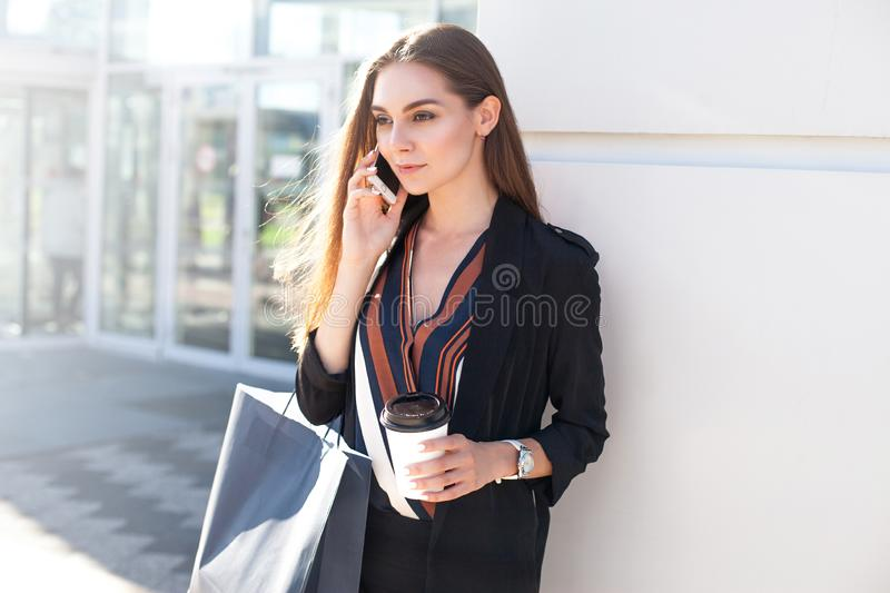 Young attractive woman enjoys phone near shopping mall with glass of coffee and package stock image