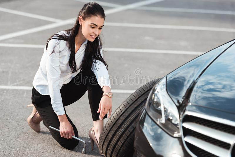 Young attractive woman in formal wear squatting near car tire with lug wrench stock images