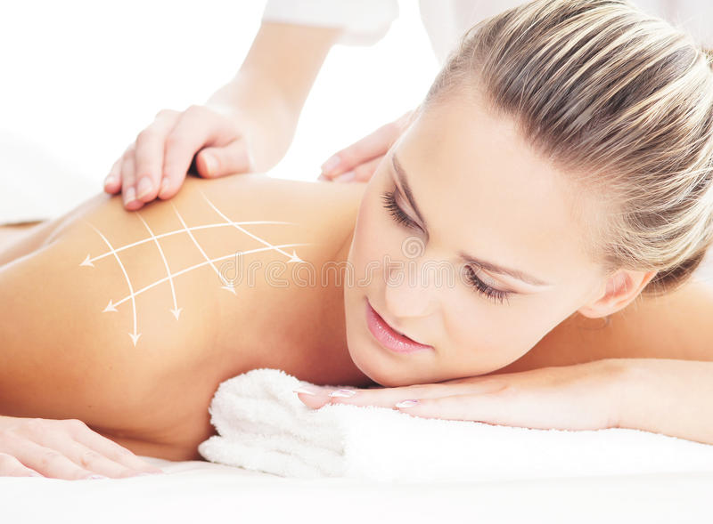 Young attractive woman getting massaging treatment. Young, beautiful and healthy woman getting alternative massage treatment (composition with the arrows stock photo