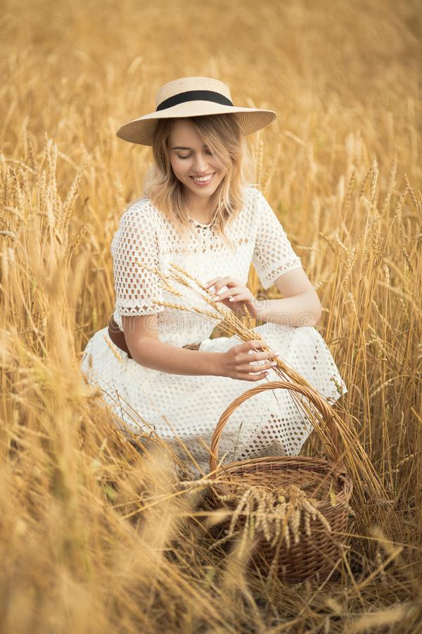 Young attractive woman and golden wheat field. royalty free stock photography