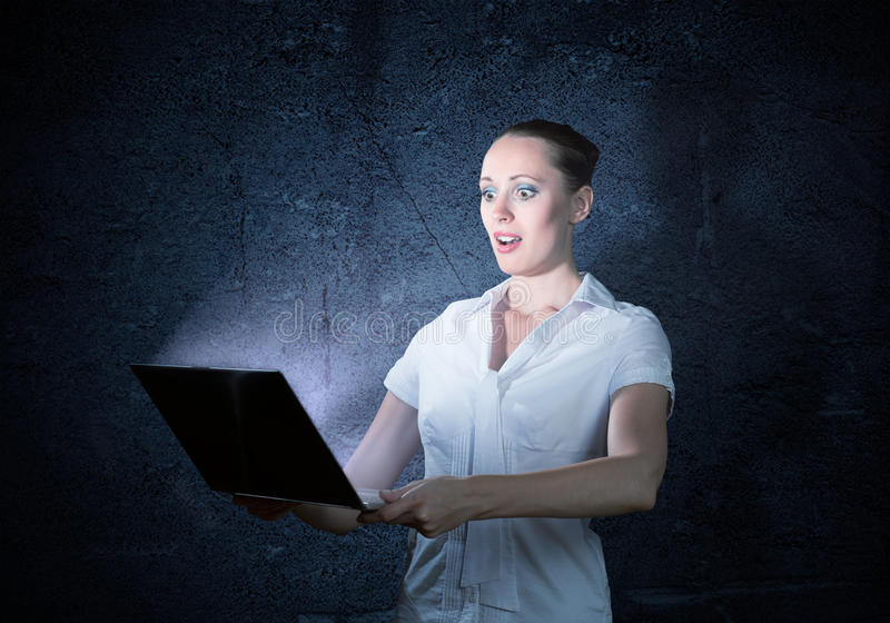Young attractive woman holding a laptop. It shines and depart monitor lights stock image