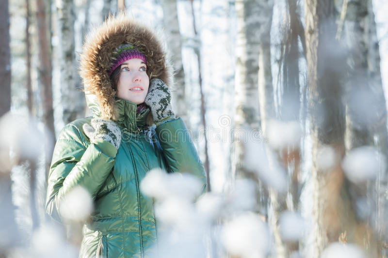 Young attractive woman holding woolly mittens near her head in winter forest outdoors. Young attractive woman is holding woolly mittens near her head in winter royalty free stock images