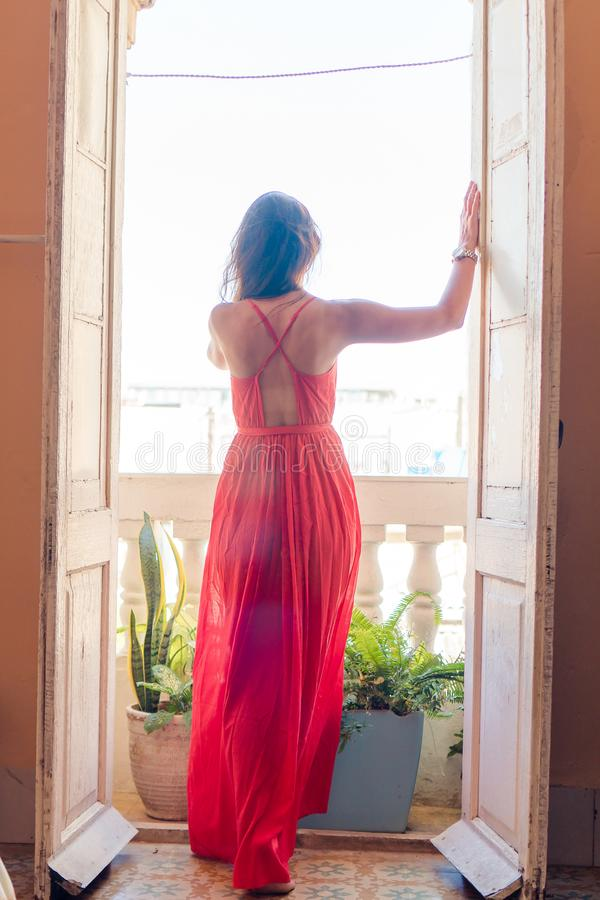 Free Young Attractive Woman In Red Dress On Old Balcony In Apartment In Havana Royalty Free Stock Images - 132171089