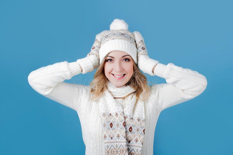 Young and attractive woman in a knitted sweater. Pulls cap, blue background royalty free stock photo