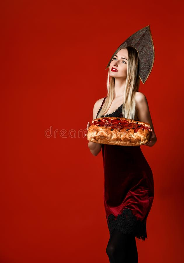 Portrait of a young beautiful blonde holding a delicious homemade cherry pie. royalty free stock photography
