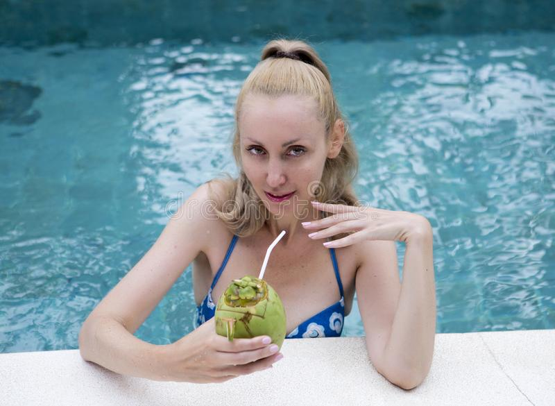 Young attractive woman with long hair in a swimwear in the pool with cocktail in coconut stock image