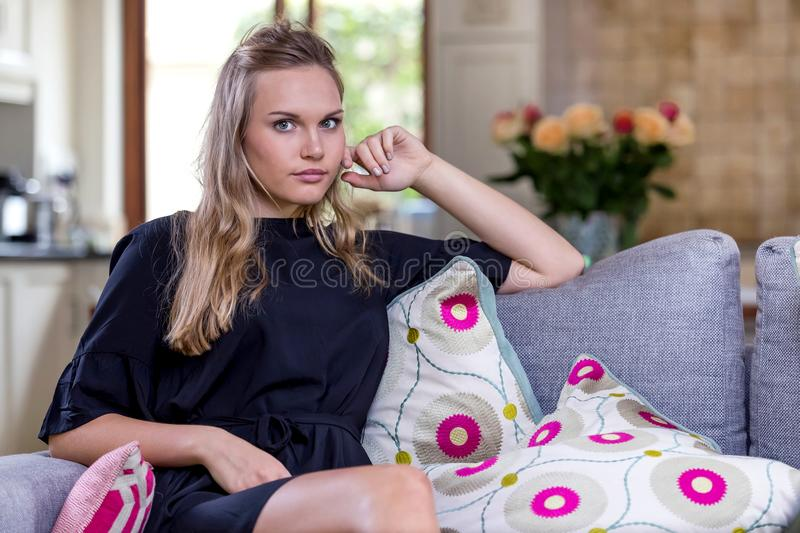 Girl sitting on sofa in a lounge. stock image