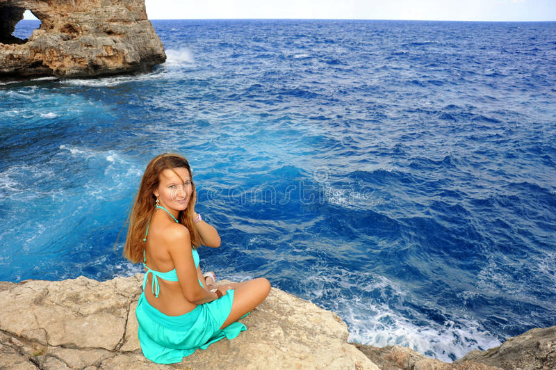 Young attractive woman looking at sea horizon sitting alone on rock cliff royalty free stock image